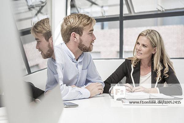 Geschäftsmann und Geschäftsfrau bei einer Bürobesprechung
