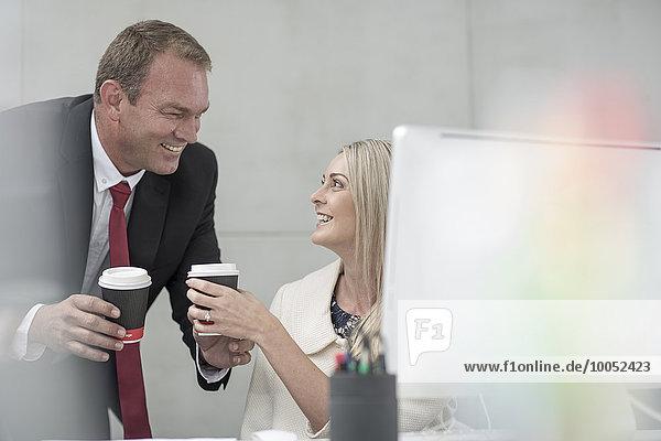 Geschäftsmann und Geschäftsfrau beim Kaffeetrinken im Büro