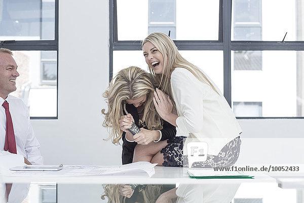 Geschäftsfrau im Büro lacht fröhlich