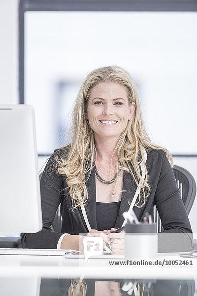 Selbstbewusste Geschäftsfrau am Schreibtisch sitzend