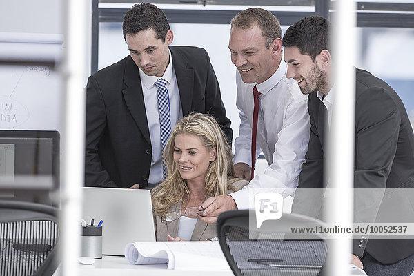 Lächelnde Geschäftsleute im Büro mit Blick auf den Laptop