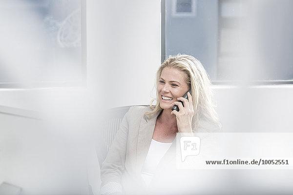 Lächelnde Geschäftsfrau im Büro am Telefon