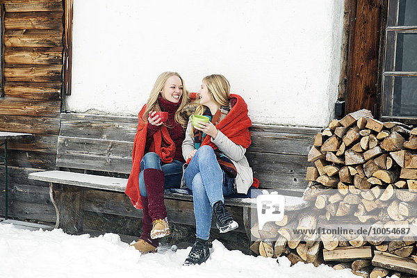 Two young female friends drinking coffee outside wooden cabin