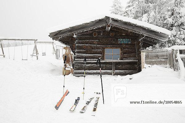 Ski und Skistöcke außerhalb des Blockhauses  Tirol  Österreich