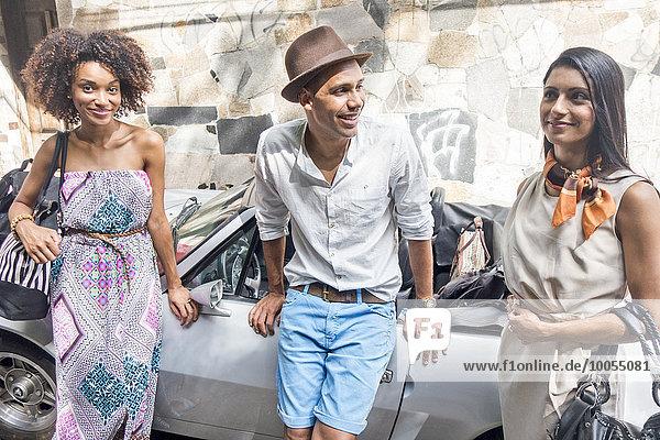 Drei Freunde stehen zusammen und lehnen sich gegen das Auto.