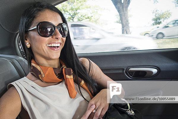 Mittlere erwachsene Frau hinten im Auto  lächelnd