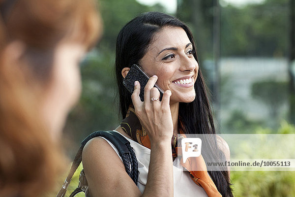Mittlere erwachsene Frau mit Smartphone  lächelnd