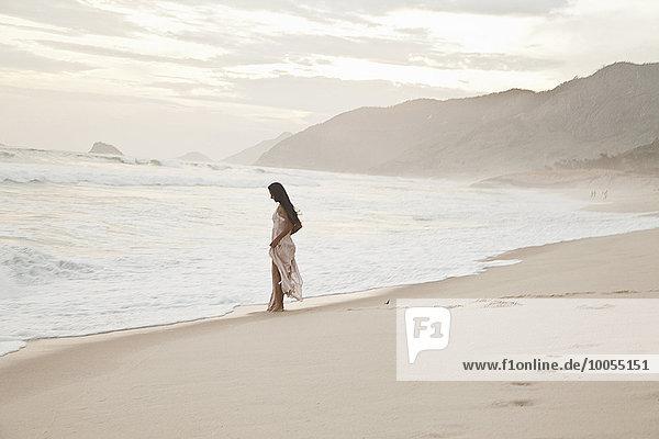 Mittlere erwachsene Frau geht am Strand entlang