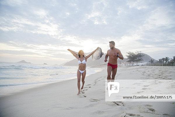 Mittleres erwachsenes Paar  das in Badebekleidung am Strand entlang läuft.