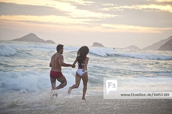 Mittleres erwachsenes Paar  das bei Flut am Strand entlang läuft  Hand in Hand  Rückansicht