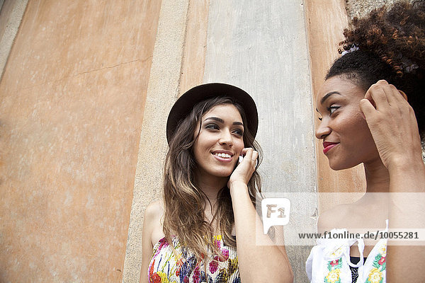Two young women standing together  using smartphone  close-up
