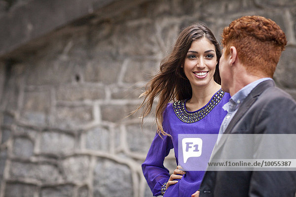 Young couple standing together  outdoors  looking away  smiling