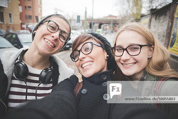 Drei Schwestern  die ein Selfie auf der Straße aufnehmen