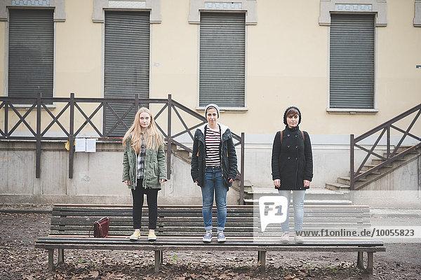 Drei Schwestern stehen auf der Parkbank