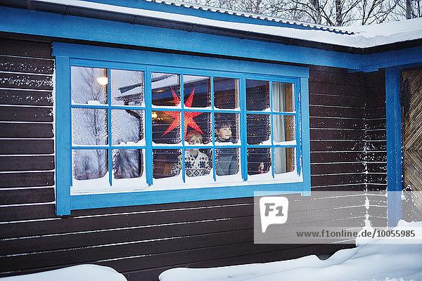 Zwei Brüder schauen zu Weihnachten aus dem schneebedeckten Kabinenfenster