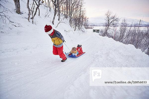Junge zieht Bruder auf Schlitten auf schneebedecktem Hügel,  Hemavan,  Schweden