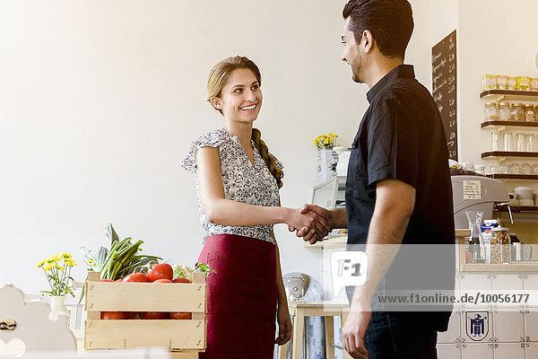 Junge Frau schüttelt Männern die Hand