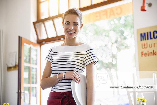 Junge Kellnerin hält Tablett lächelnd vor der Kamera