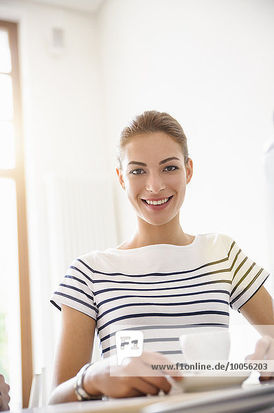 Young woman drinking coffee smiling at camera