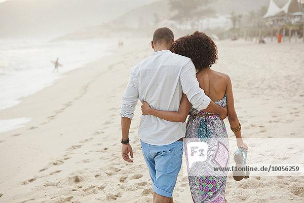 Rückansicht des Paares  das am Strand spazieren geht  Rio De Janeiro  Brasilien
