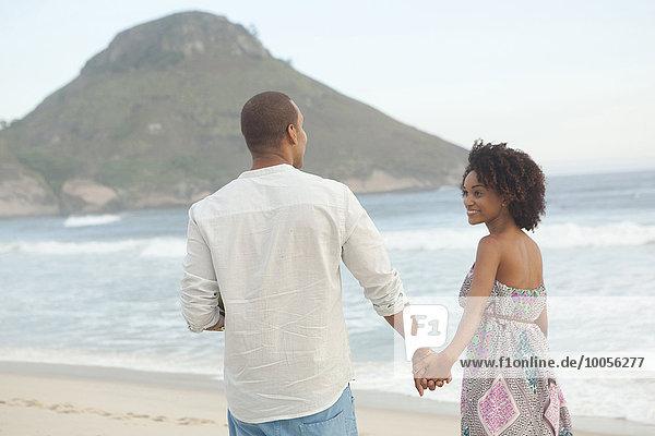 Paar  das Hand in Hand am Strand spazieren geht  Rio De Janeiro  Brasilien