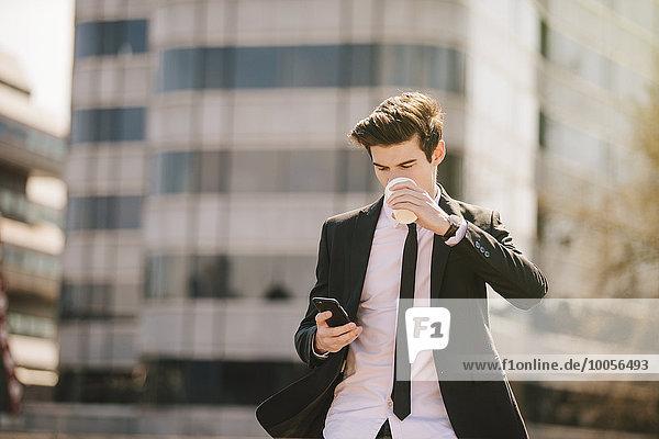 Ein junger Geschäftsmann  der Kaffee trinkt  während er Smartphone-Texte liest.