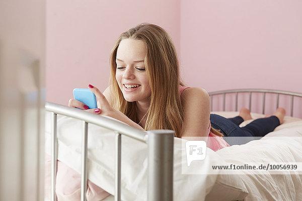 Mädchen liegt auf dem Bett und liest Textnachricht auf dem Smartphone.