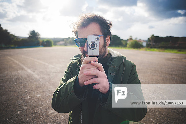 Porträt eines erwachsenen Mannes  der auf eine alte Filmkamera zeigt.