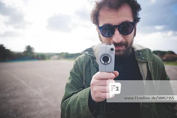 Porträt eines erwachsenen Mannes mit Vintage-Filmkamera auf Brachland
