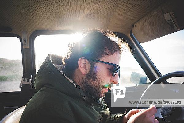 Mann im Auto am Strand beim Zigarettendrehen