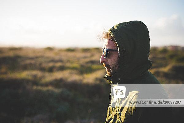 Porträt eines erwachsenen Mannes mit Anorakhaube im Feld