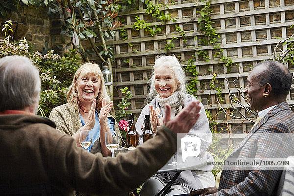 Seniorenfreunde sitzen im Garten und reden.
