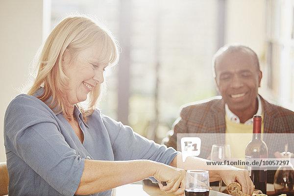 Reife Frau beim Brotschneiden  älterer Mann lächelt