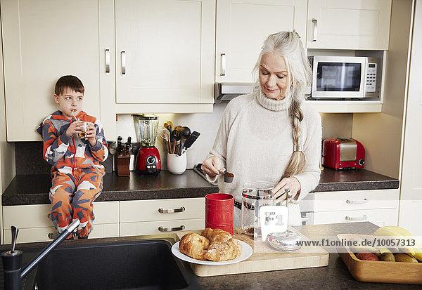 Grandmother making coffee  grandson sitting on kitchen counter