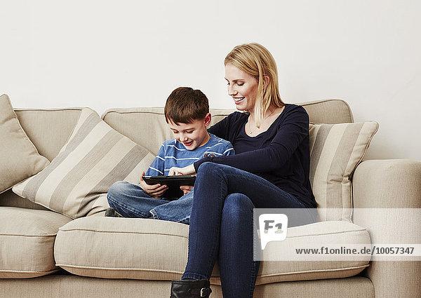 Kleiner Junge mit digitalem Tablett und Mutter