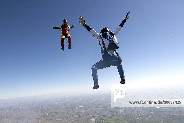 Freifliegende Fallschirmspringer im blauen Himmel