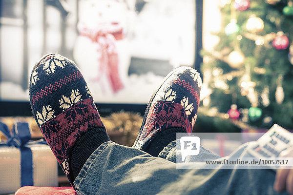 Person in Hausschuhen mit hochgezogenen Füßen