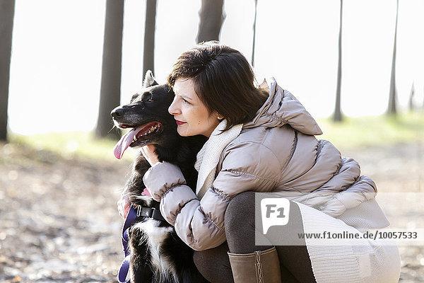 Mittlere erwachsene Frau kauernd mit ihrem Hund auf dem Feldweg