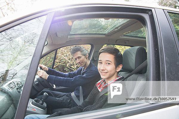Porträt eines reifen Mannes und eines jugendlichen Sohnes beim Autofahren