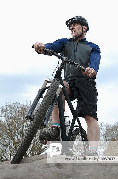 Flachwinkelaufnahme eines reifen Mountainbikers mit Blick aus der Felsformation