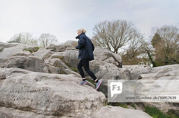 Mittlere erwachsene Läuferin  die eine Felsformation hinaufläuft.