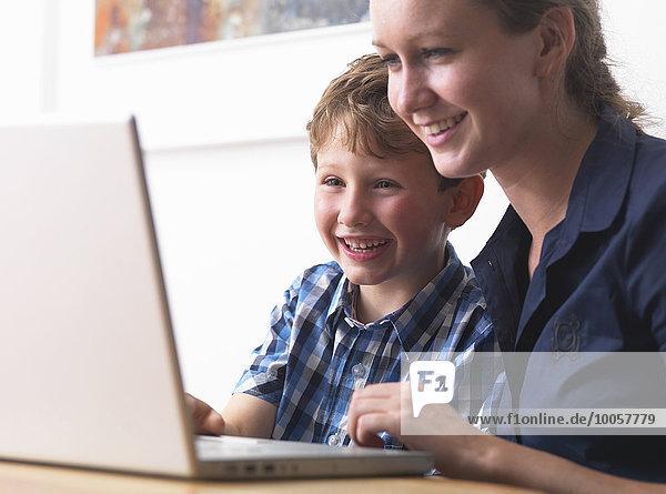 Junge Frau und Sohn mit Laptop zu Hause