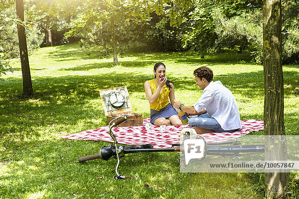Junges Paar sitzend beim Picknick auf der Decke