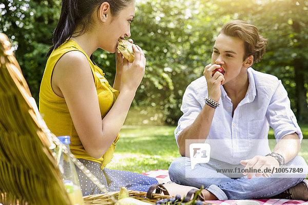 Junges Paar sitzend beim gemeinsamen Picknick