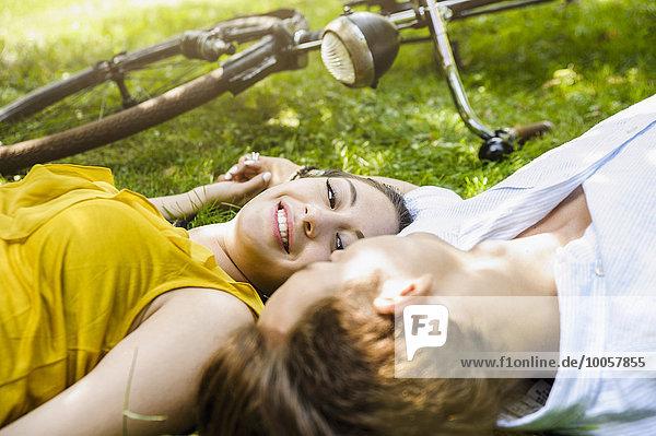 Junges Paar auf Gras liegend  Händchen haltend