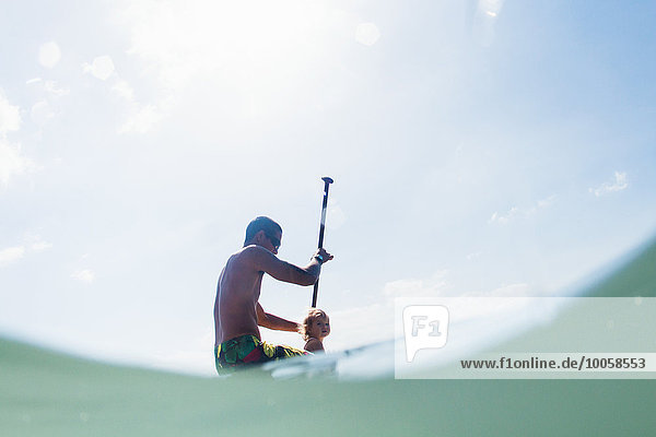 Flachwinkelansicht des jungen Mannes und der Kleinkindtochter beim Paddeln