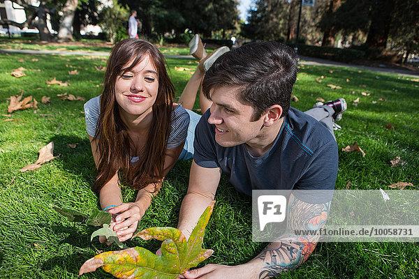 Junges Paar im Park liegend mit Herbstblatt