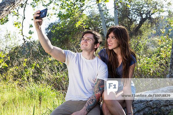 Junges Paar mit Smartphone Selfie im Park