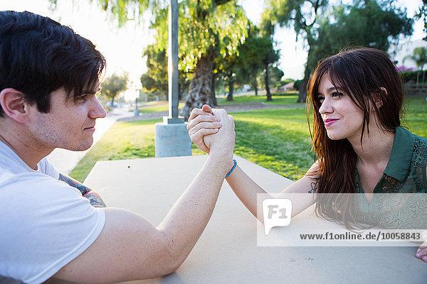 Junges Paar Armdrücken auf der Picknickbank im Park