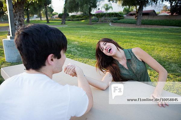 Junges Paar  das vorgibt  auf einer Picknickbank im Park zu ringen.